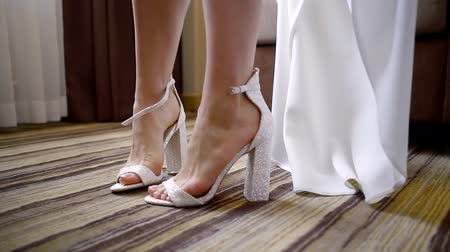 high heeled sandals : Close up. Elegant brides feet wear high-heeled shoes Stock Footage