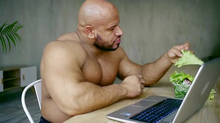 subscribers : male bodybuilder sports blogger sitting indoors at the laptop eating salad and answering questions of their Internet subscribers