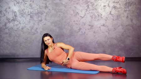 multifunctional : young athletic girl demonstration and training exercise flapping her legs up lying on her side