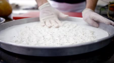 lombo de vaca : Close up. The hands of the chef in gloves prepare the base of a layer of salt on a baking sheet for baking meat