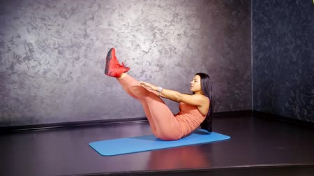 multifunctional : fitness trainer shows off a twisting exercise with a touch of raised legs up. multifunctional training