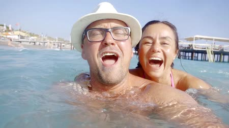curtimento : Close up portrait of a cheerful husband wearing hat and glasses and his beautiful brunette wife in the sea.