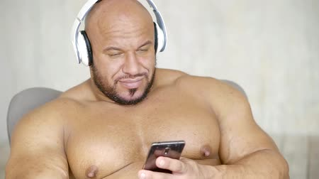 üstsüz : Handsome shirtless bodybuilder is lying on couch and listening to music in wireless headphones.