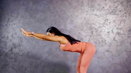 tilts : girl fitness trainer demonstration of stretching exercises tilts forward into the horizon. pull legs and shoulders
