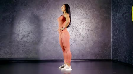 tilts : girl fitness trainer demonstration of stretching exercises tilts back in half amplitude