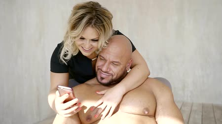 öz : happy blonde woman is hugging her husband sitting in a chair and taking selfie on camera of smartphone, loving spouses