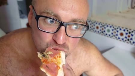 palačinka : man wearing glasses eating pizza with ham and mushrooms at home in the kitchen
