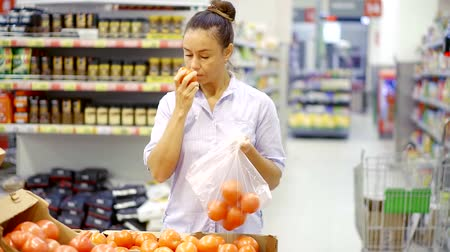 мускусная дыня : woman chooses red tomatoes and put them in a plastic bag in a supermarket