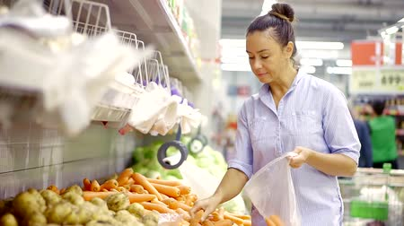 мускусная дыня : Slender woman buys carrots and put them in a plastic bag in the supermarket