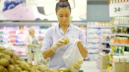 мускусная дыня : Slender woman buys potatoes and put them in a plastic bag in the supermarket
