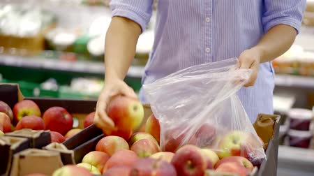 мускусная дыня : close up. women hands recruit red apples in plastic bag in supermarket