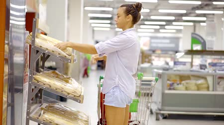 takes : buying food at the supermarket. a woman carries a cart and takes two long French loaf