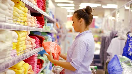 мускусная дыня : shopping at the supermarket. a woman chooses a soft bath towel for her family