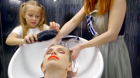 peruca : head washing procedure in the beauty salon. the girl helps to comb wet hair client