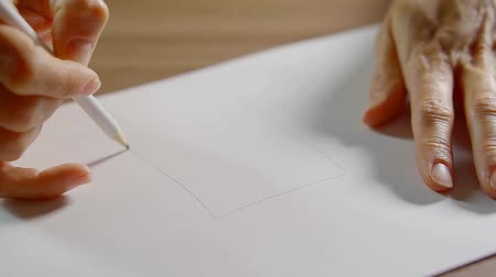 grafit : close up. womans hands draw pencil on a white sheet simple layout of the house Stok Video