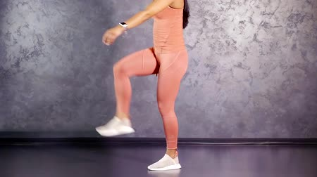 him : young girl fitness trainer shows exercise lifting straight leg in front of him with a touch of the palm