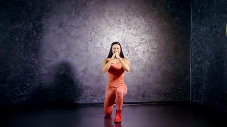 quadriceps : young girl coach in a sports jumpsuit shows an exercise lunge on the spot. target muscle group quadriceps, biceps thighs and buttocks Stock Footage