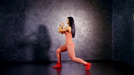 quadriceps : young girl coach in a sports jumpsuit shows an exercise lunge on the spot. training quads, hamstrings and glutes.