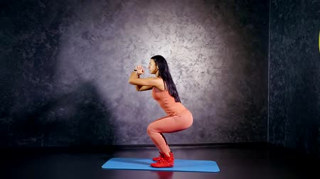 staging : young girl trainer in a sports jumpsuit shows exercise squats in the horizon with a narrow staging legs Stock Footage