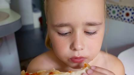 eye piece : small hungry preschooler girl is biting and chewing piece of juicy tasty pizza in a room, close-up Stock Footage