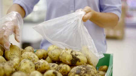 jelölőnégyzetet : female customer is taking potatoes by weight in a food shop, choosing from a box and putting in plastic bag