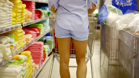 troli : young slim woman is moving along shelves with towels in a store, pushing a trolley for purchases