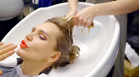 fénypont : stylist is washing hair of blonde woman visitor of a barbershop in a sink, close-up of female face