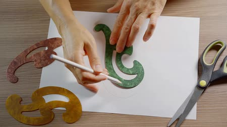 quilling : woman is drawing on a paper sheet, outlining a plastic curve template, using pencil, close-up