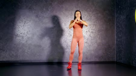 crouch : female fitness trainer is squatting with lunges in a gymnastic room and smiling, looking in a camera Stock Footage