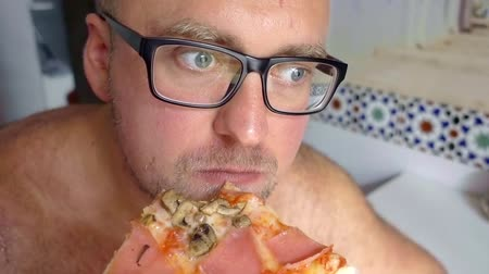 home grown : Close up shot of a bald man in glasses eating a big slice of a pizza with meat and vegetables. Stock Footage