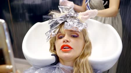 щетка для волос : Close up shot of a beautiful woman having her hair dyed in a hair salon.