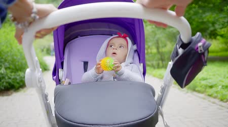 babygirl : Parents take daughter for a walk in a stroller in summer. Stock Footage