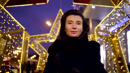 warms : portrait of a middle-aged woman walking holiday city lights lights and animation. warm black fur coat warms you in the winter night sweet girl