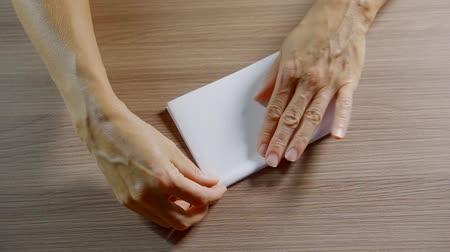 dobrado : close up. woman hands folded neatly from a sheet of white fake paper