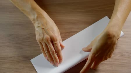 сложены : close up. woman hands folded rectangular blank sheet of white paper