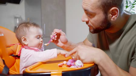 bottle feeding : Handsome young father feeding to his baby food in the kitchen. He is making faces and feeding his daughter. Father and daughter time.