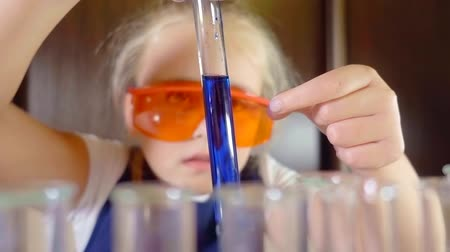 kap : child girl in safety glasses orange watching the reaction of the reagent in the test tube in chemistry class Stock mozgókép