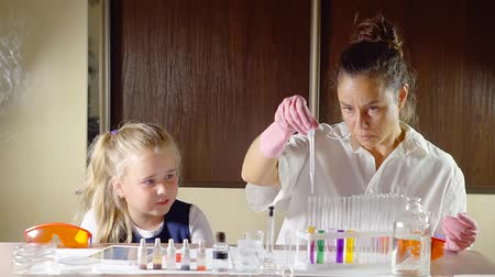 acadêmico : lesson in school on the chemistry of color depending on the acidic or alkaline environment. teacher dripping the reagent into a test tube student girl watched in amazement the reaction Stock Footage
