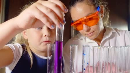 kap : girl student shows the teacher the result of their work in chemistry showing the color of the substance in test tubes