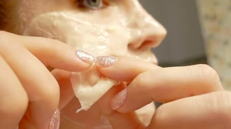 melisa : close up. girl in her bathroom removes facial cleansing gel mask from the skin Stok Video