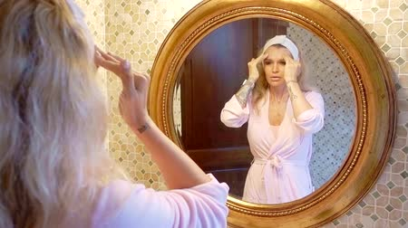 melisa : attractive blonde is standing in her bathroom and applies a moisturizer to the skin in front of a round mirror