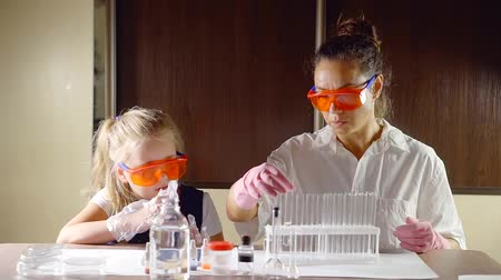 gaining : school chemistry class. the teacher is a woman in protective clothing is gaining the reagents in the test tubes for the reaction changes wisheswe