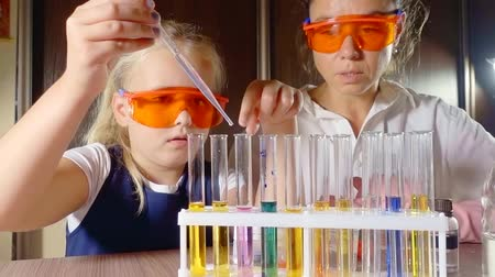 příklad : laboratory work on mixing reagents with colors of different colors. chemistry lesson at school with practical work. the teacher guides the learner