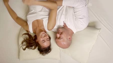 noční prádlo : Adult couple in bed in the evening lying down. the man cheers his beloved woman, they are smiling and happy