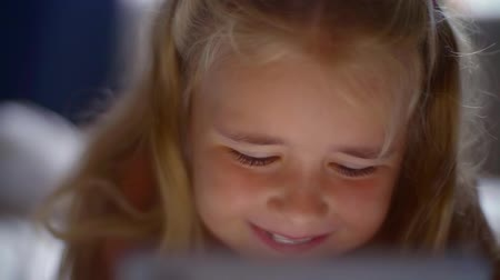 ebook : Happy smiling child lying in bed and enthusiastically playing the game on the smartphone. The childs face is illuminated by a bright monitor