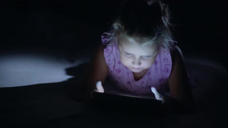 ebook : Night shot of kids girl face browsing tablet pc with light reflection on it