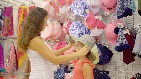 sorriso largo : brunette woman is putting big hat on a head of her little daughter in a clothing store, choosing accessories