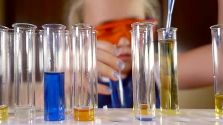 analyzes : child girl is performing chemical experiments with liquids in a laboratory alone, dripping reagent