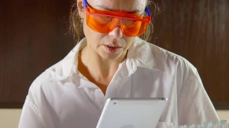 analyzes : chemist woman is wearing protective glass is reading from display of a tablet in a laboratory