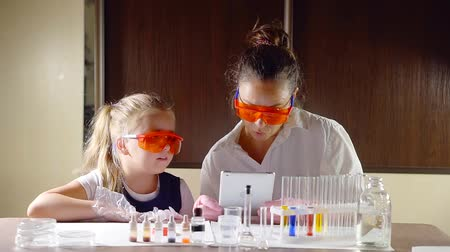 parenthood : cute mother and daughter are playing in toy chemistry laboratory, reading instruction on a screen of a tablet